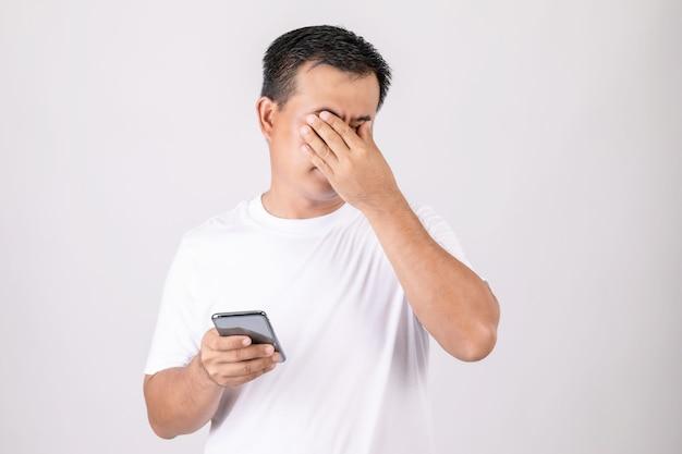 Uomo che tocca gli occhi a causa del dolore causato dall'utilizzo eccessivo dello smartphone