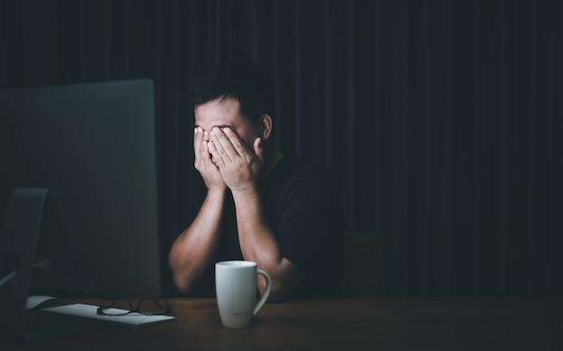 Uomo che tocca i suoi occhi a causa del lavoro sul computer