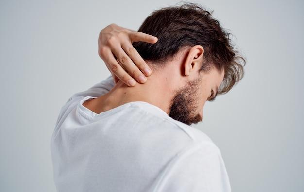 Uomo che tocca il collo con il mal di schiena osteocondrosi della mano