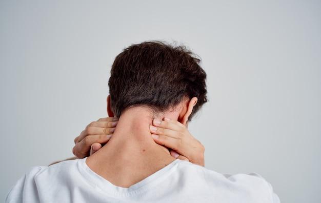 Uomo che tocca il collo con il mal di schiena osteocondrosi mano