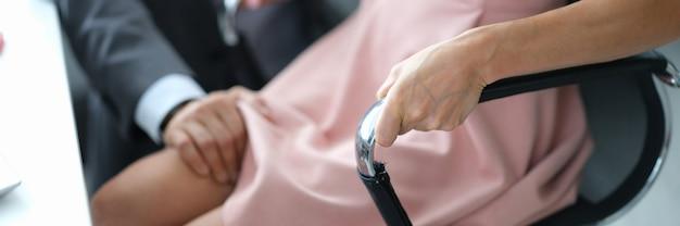 Uomo che tocca il ginocchio della segretaria e molestie sessuali al lavoro