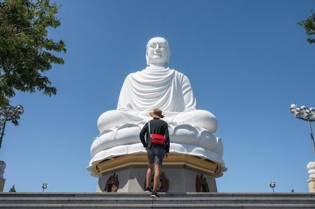 Turista dell'uomo che sta sulle scale con il grande buddha e cielo blu nel tempio della pagoda di long son a nha trang, vietnam