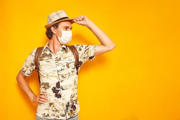 Turista uomo con zaino in maschera medica tiene il cappello e distoglie lo sguardo isolato su sfondo giallo