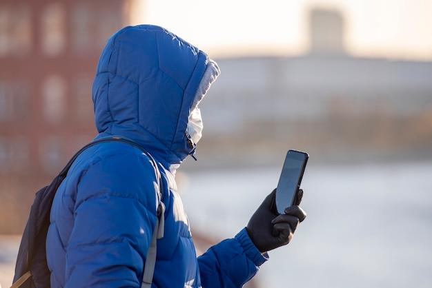 Un uomo, turista con maschera di protezione medica e guanti utilizzando il cellulare