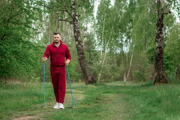 Un uomo in tuta è impegnato nel nordic walking