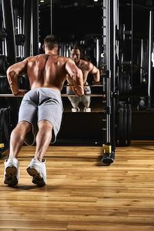 Un uomo allena le braccia e il petto in palestra sul simulatore, fa esercizi per diversi gruppi muscolari.
