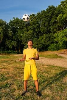 L'uomo allena e migliora il controllo del pallone da calcio sulla riva sabbiosa erbosa del fiume