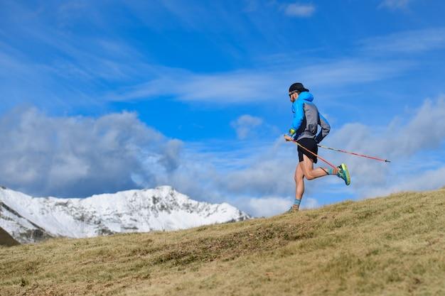 Un uomo si allena per l'ultra run trail in montagna in autunno con la prima neve in montagna