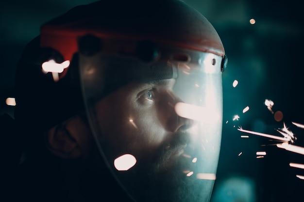 Uomo in maschera protettiva trasparente con scintille volanti nell'oscurità
