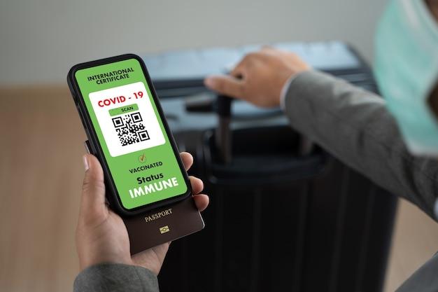 L'uomo viaggia sulla mappa del passaporto dell'immigrazione per mostrare un certificato di vaccinazione contro il covid-19 in aeroporto