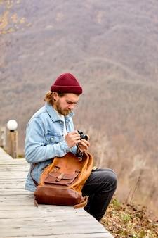 L'uomo fotografo blogger di viaggio con la fotocamera si siede a configurare la fotocamera per scattare foto di montagne ...