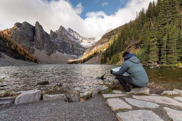 Viaggiatore dell'uomo seduto e guardando la mappa sul lago agnes al parco nazionale di banff