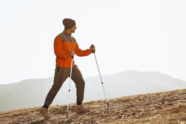 Viaggiatore dell'uomo in abbigliamento sportivo con bastoncini da trekking salendo la montagna