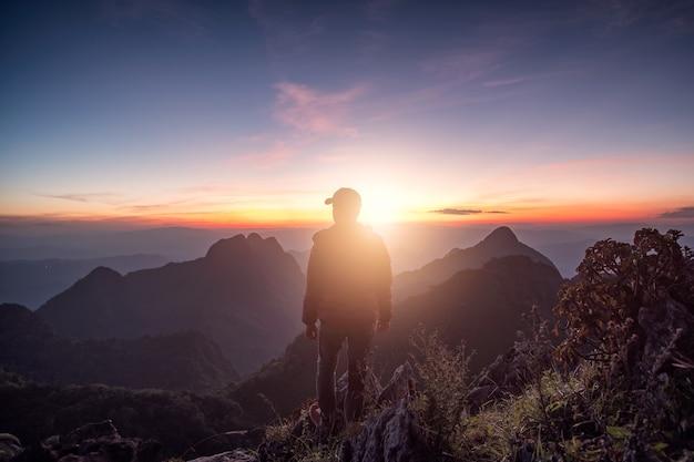 Viaggiatore dell'uomo in piedi sulla cresta di roccia con la luce solare nel santuario della fauna selvatica al tramonto