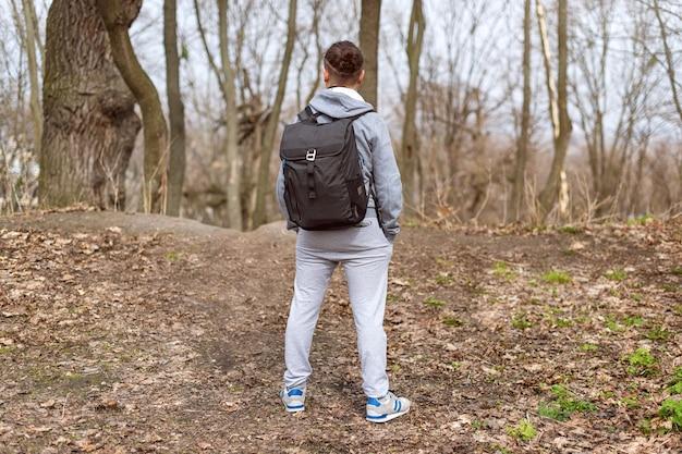 Viaggiatore dell'uomo con lo zaino che fa un'escursione nella foresta di primavera, che riposa sulla cima della collina