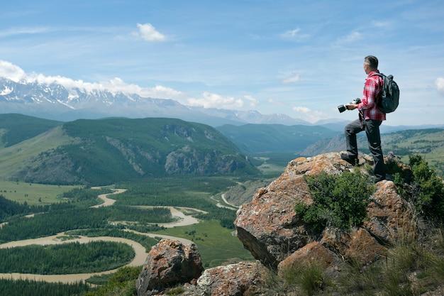 Uomo viaggiatore con zaino scattare foto in cima alla montagna. viaggio e concetto di stile di vita attivo.