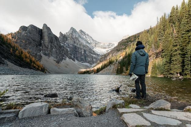 Viaggiatore dell'uomo con la mappa che sta sul lago agnes al parco nazionale di banff