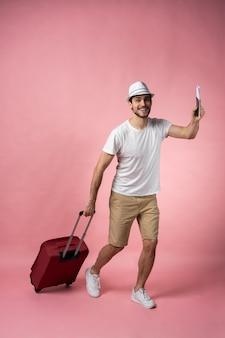Viaggiatore dell'uomo con valigia, passaporto e biglietto.