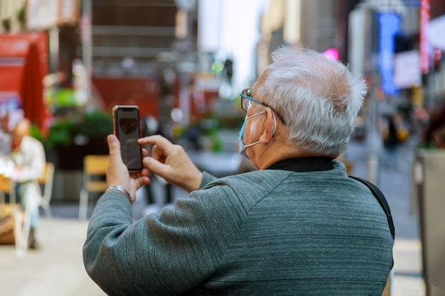 Uomo che viaggia guardando nello smartphone di times square, manhattan, new york city su indossare una maschera per il viso