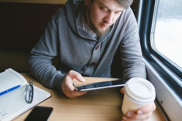 L'uomo viaggia in treno seduto vicino al finestrino utilizza un tablet
