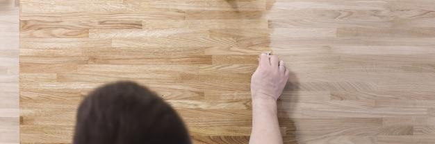 L'uomo tratta la superficie in legno del tavolo con una vernice protettiva