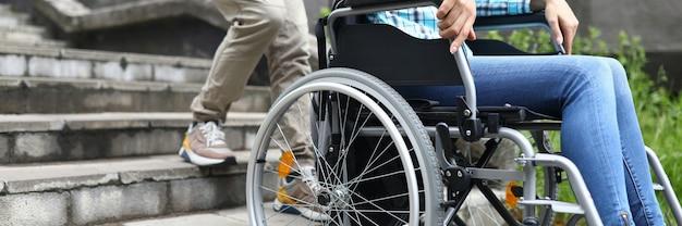 L'uomo cerca di trascinare la sedia a rotelle con la donna sulle scale