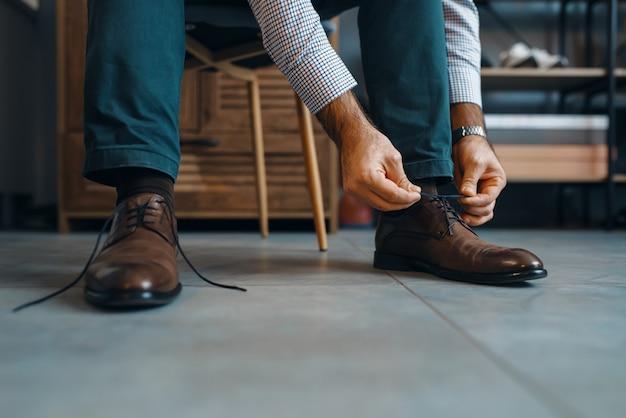 L'uomo prova scarpe riparate, servizio di riparazione di calzature. abilità artigiana, laboratorio di calzoleria, capolavori con stivali, negozio di calzolai