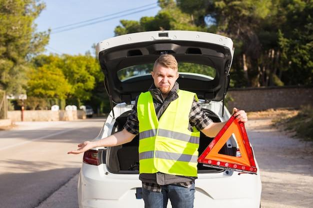 All'uomo che ha problemi con un'auto riceve un segnale di emergenza triangolare rosso