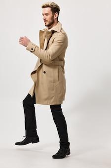 Un uomo in pantaloni e cappotto beige corre di lato su uno sfondo chiaro