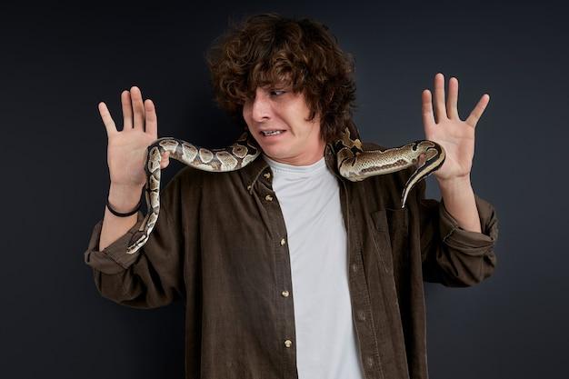Uomo che cerca di mantenere la calma mentre il serpente esotico sta strisciando su di lui, isolato sul muro nero