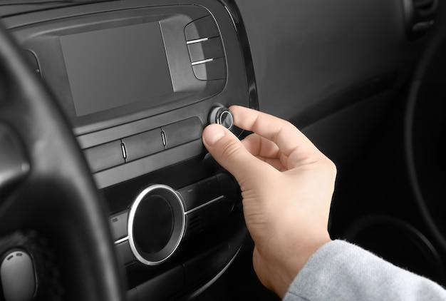 Uomo che sintonizza la radio in auto