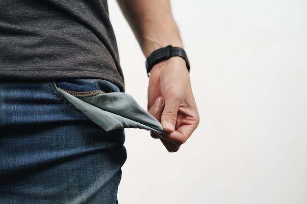 Uomo che gira la tasca dei jeans per mostrare la tasca vuota. bancarotta, cattiva economia, nessun concetto di denaro.