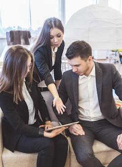 Un uomo e due donne in giacca stanno discutendo di lavoro durante una riunione di lavoro. stanno guardando il tablet
