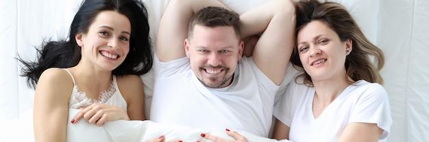 Uomo e due donne sdraiate a letto vista dall'alto sesso promiscuo concept