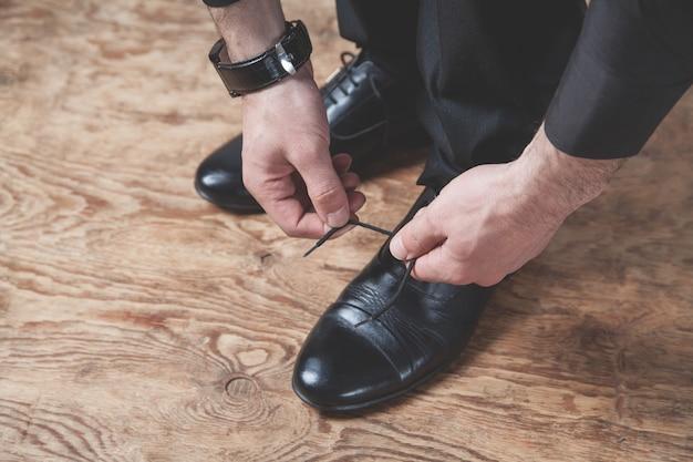Uomo che lega i lacci delle scarpe.
