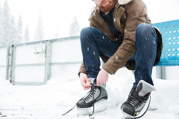 Uomo che allaccia i lacci delle scarpe sui pattini da ghiaccio all'aperto