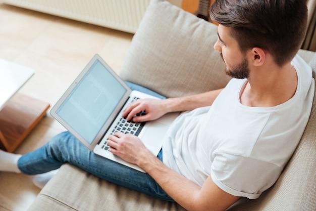 Uomo che digita del testo sul computer portatile sul divano di casa