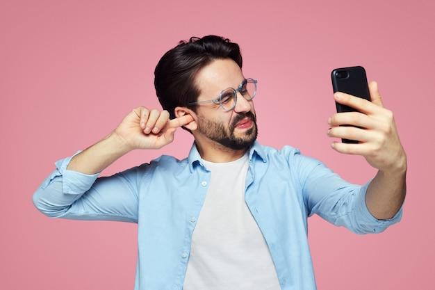Uomo che pulisce in modo antigienico l'orecchio usando il dito mentre parla sul viso