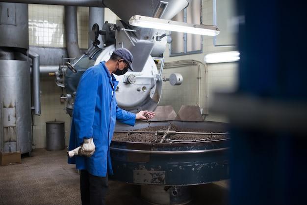 Uomo in uniforme che controlla la qualità del caffè tostato. torrefattore che lavora su attrezzature per la torrefazione. uomo in maschera e uniforme che lavora con l'apparecchio dei macchinari