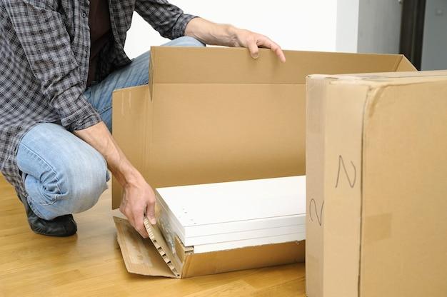Uomo che disimballa una scatola di cartone con mobili