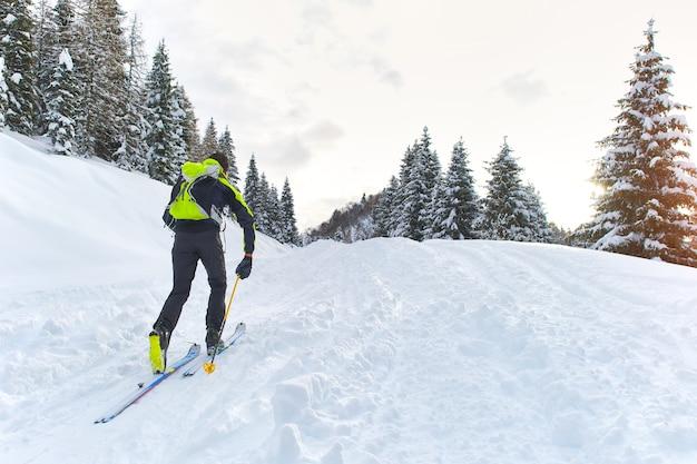 Uomo in salita con gli sci con le pelli sotto