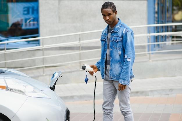 L'uomo usa lo smart phone durante l'attesa e l'alimentazione si collega ai veicoli elettrici per caricare la batteria in auto