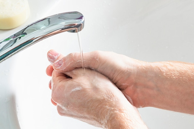 L'uomo usa sapone e lavarsi le mani