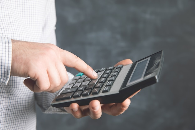 Un uomo usa una calcolatrice.