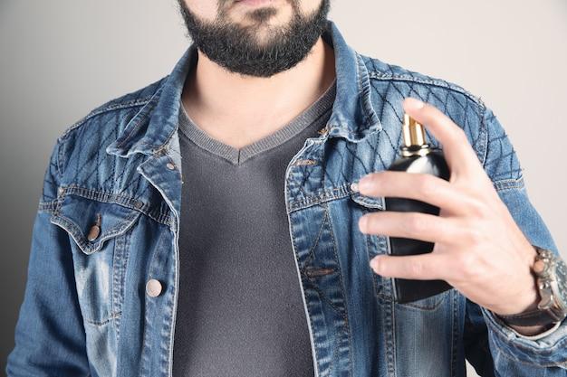 L'uomo usa il profumo maschile su se stesso