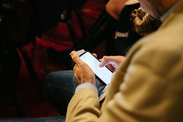 L'uomo usa un telefono cellulare in un congresso