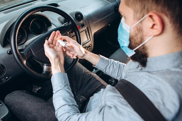 L'uomo usa disinfettante mentre guida l'auto. precauzioni durante l'epidemia di coronavirus. uomo in maschera medica in auto.