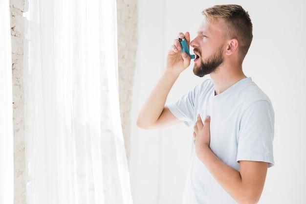 Uomo che usa l'inalatore per l'asma Foto Premium