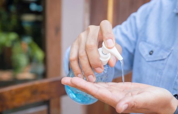 Uomo che utilizza una bottiglia di sapone disinfettante antibatterico. disinfettante per le mani gel alcolico strofinare le mani pulite igiene prevenzione dello scoppio del virus del coronavirus