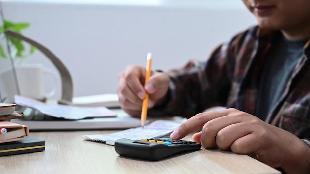 Uomo che usa la calcolatrice per calcolare le bollette a casa.